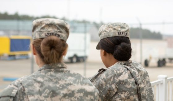 Two female soldiers look out over an airport
