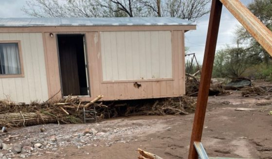The Lashers' home, shown pushed 30 feet away from the back steps by the floodwaters.