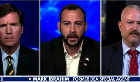 Former DEA agent Mark Ibrahim, center, speaks with Fox News host Tucker Carlson, left, and attorney Darren Richie concerning the charges he is facing for being outside of the Capitol on Jan. 6.