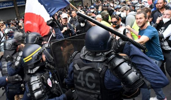 Protesters stand in front of riot police during a demonstration against French legislation making a COVID-19 health pass compulsory to visit a cafe, board a plane or travel on an inter-city train in Paris on Saturday.