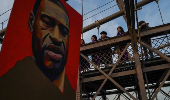 Spectators watch marchers cross the Brooklyn Bridge demanding police reform after a commemoration to honor the anniversary of George Floyd's death on May 25, 2021, in New York City.