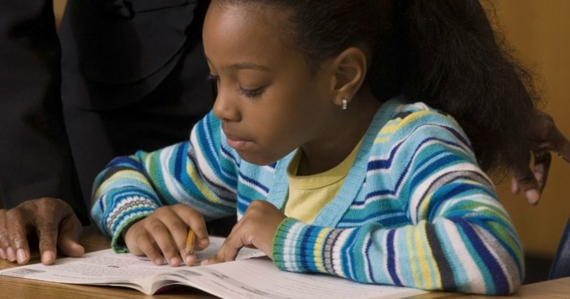 A young female student works in her workbook as a teacher looks over her shoulder.