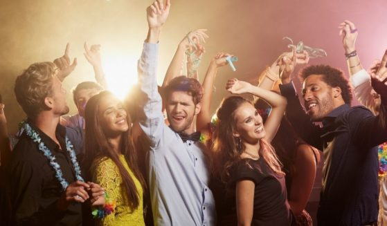 This stock photo portrays a group of friends dancing to music. Greece announced Saturday that music will be banned around the clock until the end of the month on the popular tourist island of Mykonos in response to an increase in COVID cases.