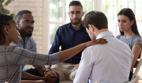 A group of people are seen comforting their friend in the stock image above.