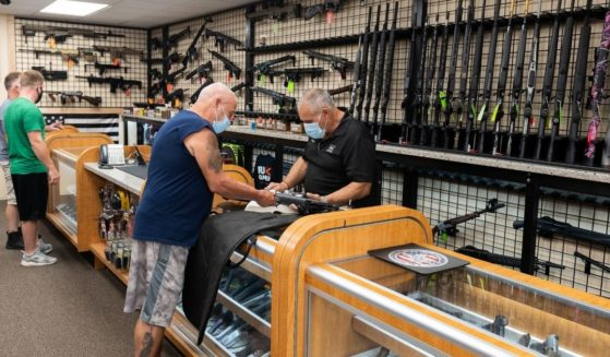A gun shop employee shows guns to customers at SP Firearms Unlimited on Aug. 6, 2020 in Franklin Square, New York.