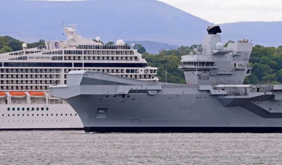 The Royal Navy aircraft carrier HMS Queen Elizabeth passes a cruise ship as she leaves the Forth Estuary following a period of planned maintenance in Rosyth Dockyard where she was built on May 23, 2019, in North Queensferry, Scotland.