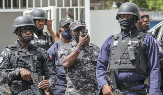 Leon Charles, head of the Police Nationale of Haiti, center, gives orders on a walkie-talkie as the crowd surrounds the Petionville Police station where armed men were accused of being involved in the assassination of President Jovenel Moïse in Port-au-Prince on Thursday.