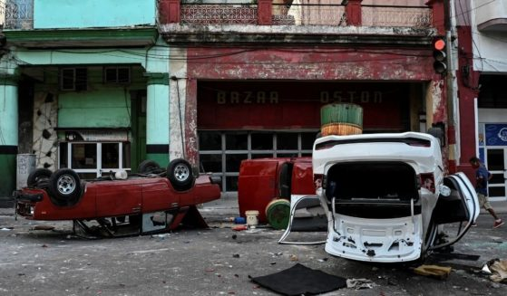Police cars are seen overturned in the street in the framework of a demonstration against Cuban President MiguelDíaz-Canel in Havana on July 11, 2021.