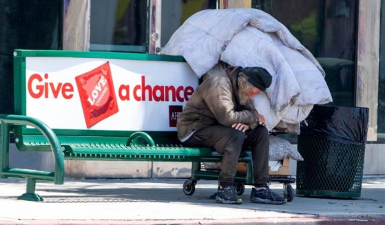 A homeless man sits on a bench on La Brea Ave on National May Day amid the COVID-19 pandemic on May 1, 2020, in Los Angeles.