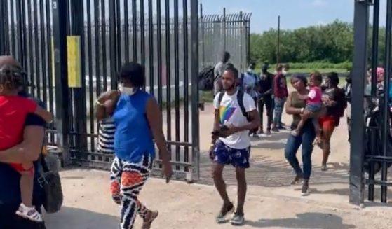 Illegal immigrants walk through a border gate into Del Rio, Texas.