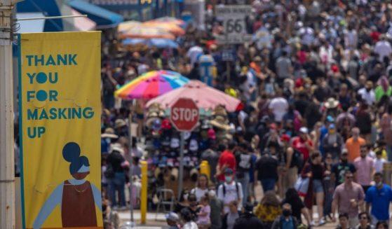 People walk near the Santa Monica Pier in Santa Monica, California, on May 31, 2021.