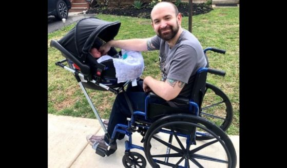 """Jeremy King and his son, Phoenix, using the device that students at Bullis School designed and built for him as part of their """"Making for Social Good"""" course."""