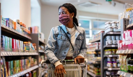 The above stock photo shows a customer at a grocery store with a face mask on.