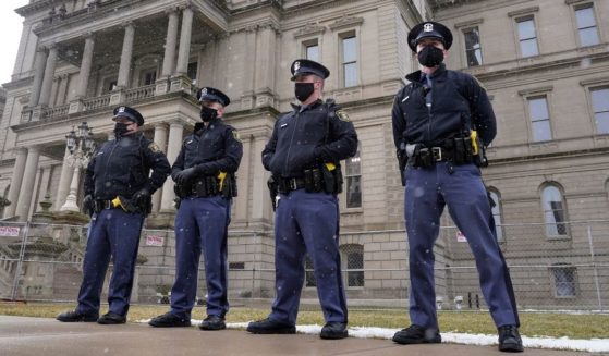 Michigan State Police troopers stand guard outside the state capitol in Lansing on Jan. 17.