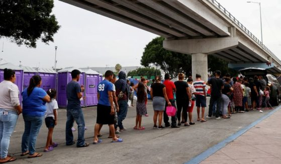 Asylum-seeking migrants wait in line for donated food at a makeshift migrant camp on the Mexican side of the San Ysidro Port of Entry on Thursday in Tijuana, Mexico.