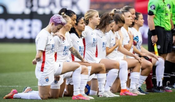 The starting lineup for the OL Reign, including Megan Rapinoe, left, kneel for the national anthem before the match against NJ/NY Gotham FC at Red Bull Arena on June 5, 2021, in Harrison, New Jersey.