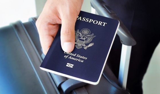 A man holding a passport is pictured in the stock image above.