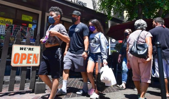 Face masks continue to be worn as people walk past restaurants open for business in Los Angeles on June 14, 2021.