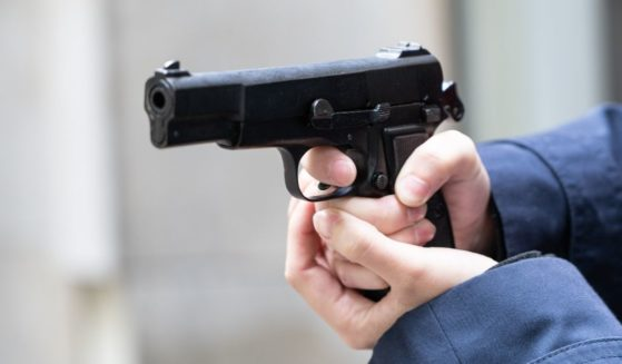This stock photo portrays a person pointing a pistol. One Texas family reported an armed run-in with a man who was allegedly spying on their 10-year-old daughter.