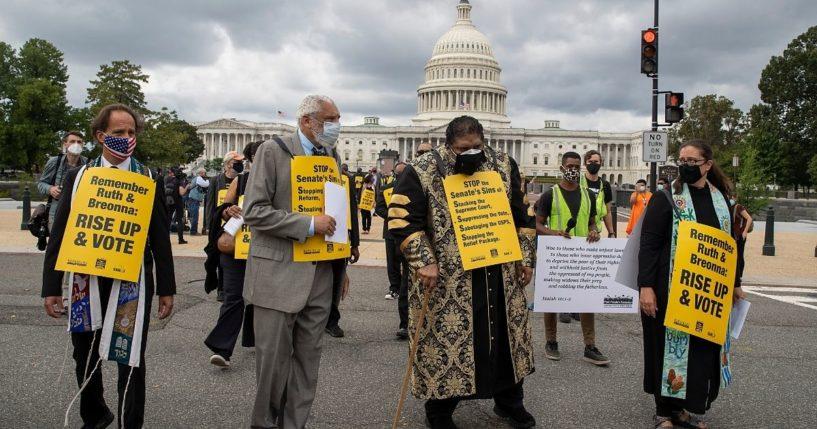Leftist activists including the Rev. Dr. William Barber, center, pray on Capitol Hill on Sept. 29, 2020, in Washington, D.C.
