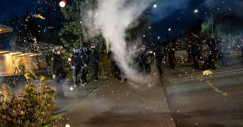 A firework explodes near Portland police officers during a protest on April 12, 2021, in Portland, Oregon.