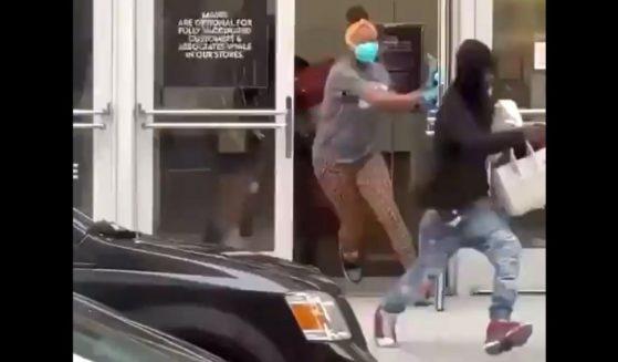 Handbag thieves run from a Neiman Marcus store in San Francisco.