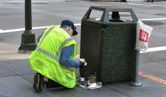 A city worker paints a trash receptacle