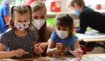 Pupils, wearing face masks, listen to their teacher during a summer project at the primary school Sonnenschule in Beckum, western Germany, on July 6, 2021.