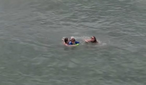 Travis Shrout helping Ashley Batchelor and her son Conner get back to shore after they got caught in a riptide.