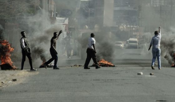 Protesters gesture toward police officers (not seen) as they burn tires in Jeppestown, Johannesburg, on Sunday.