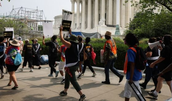 """People arrive for the """"Women's Moral Monday March on Washington"""" rally organized by the Women's March and Poor People Campaign in front of the U.S. Supreme Court on Monday in Washington, D.C."""