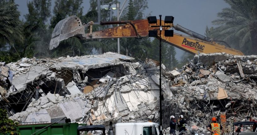 Excavators dig through the remains from the collapsed 12-story Champlain Towers South condo building on Friday in Surfside, Florida.