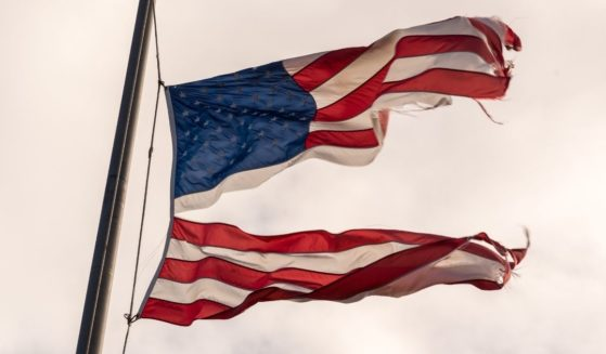 An American flag torn in half is pictured in the stock image above.