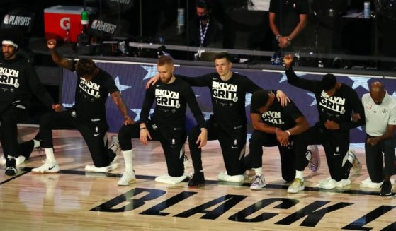 Brooklyn Nets players kneel for the national anthem before action against the Toronto Raptors in game four of the first round of the NBA playoffs at The Field House at ESPN Wide World Of Sports Complex on Aug. 23, 2020, in Lake Buena Vista, Florida.