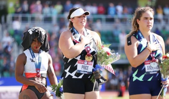 """Protesting Olympian Gwen Berry, left, with a T-shirt over her head after winning a bronze medal at the Olympic trials in Eugene, Oregon, June 26. Meanwhile, gold medalist hammer thrower DeAnna Price, center, and silver medalist Brooke Andersen, right, respectfully hold their hands over their hearts while """"The Star-Spangled Banner"""" is played."""