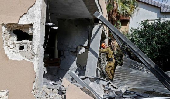A member of an Israeli rescue team inspects a house hit by a rocket fired from the Gaza Strip on May 20, 2021. Israel and the Palestinians are mired in their worst conflict in years.