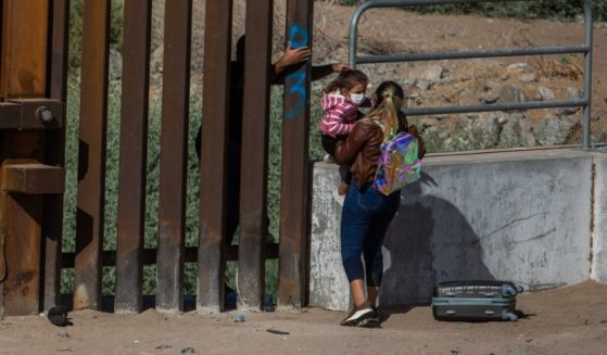 A family of asylum seekers from Cuba go around an open section of wall at the US-Mexico border to turn themselves in to Border Patrol agents in a photo taken May 13.