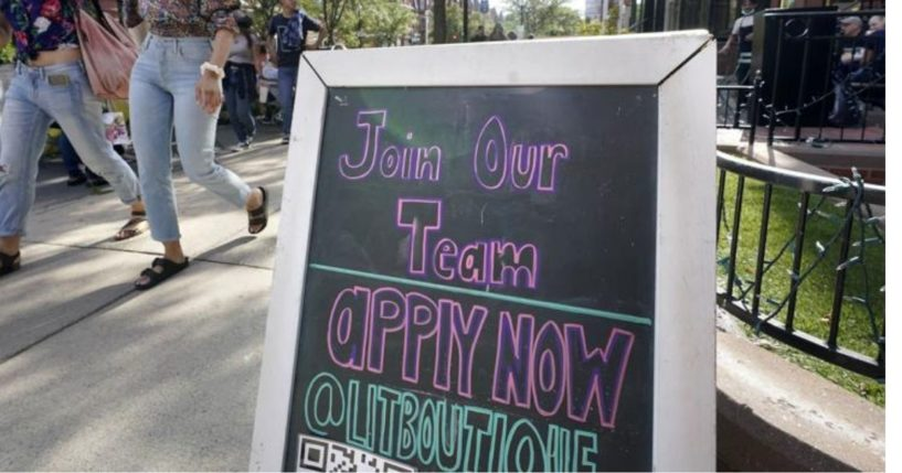 Pedestrians walk past a sign inviting people to apply for employment at a shop in Boston's fashionable Newbury Street neighborhood on Monday.
