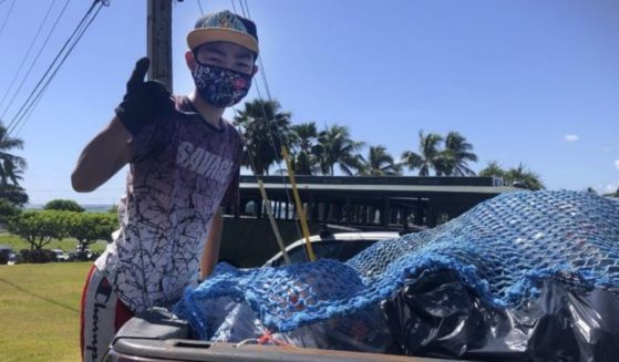 Genshu Price stands on the back of a truck after loading it with recyclable cans and bottles from Kualoa Ranch in Kāne'ohe, Hawaii, for his fundraiser, Bottles4College, in May.