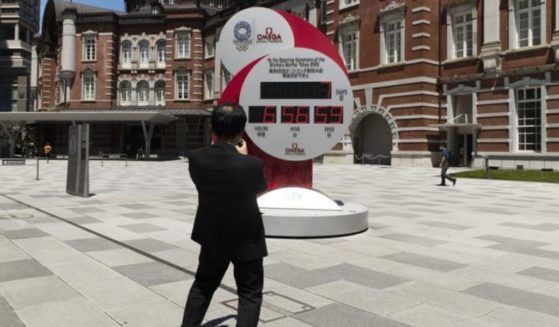 A man takes a picture of a countdown clock that shows seven more days to go before the opening ceremony of the Olympic Games in Tokyo on Friday.