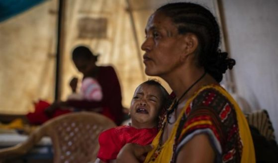 In this Tuesday, May 11, 2021 photo, Roman Kidanemariam, 35, holds her malnourished daughter, Merkab Ataklti, 22 months old, in the treatment tent of a medical clinic in the town of Abi Adi, in the Tigray region of northern Ethiopia.