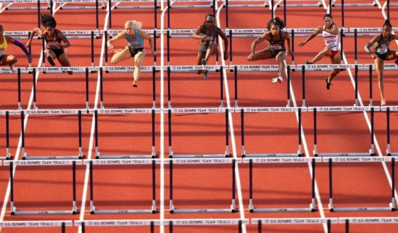 A group of female athletes runs over hurdles at the Hayward Field in Eugene, Oregon, on June 19, 2021.