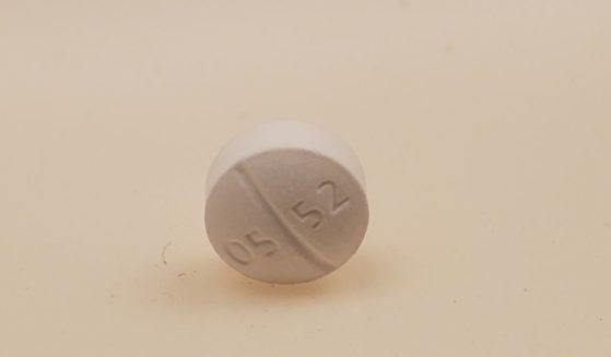 Close-up of a white Oxycodone Hydrochloride 5 mg pill, marked 05 52, resting on its edge on a white surface, photographed in Lafayette, California, May, 2021.