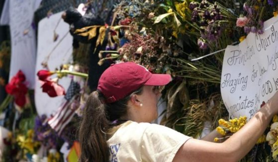 Molly MacDonald, with Mercy Chefs, hangs a sign on behalf of Princeton Church at a makeshift memorial remembering the victims of the nearby collapsed Champlain Towers South building, Wednesday in Surfside, Fla. Mercy Chefs has set up a mobile kitchen to feed search and rescue teams working at the site three meals a day.