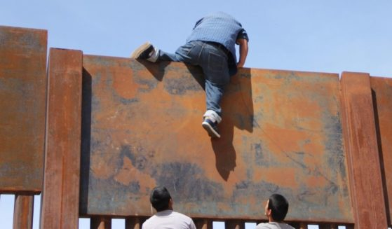 Young Mexicans help a compatriot to climb the metal wall that divides the border between Mexico and the U.S. to cross illegally to Sunland Park, New Mexico, from Ciudad Juarez, Mexico, on April 6, 2018.