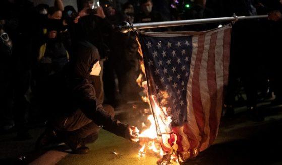 Black bloc protesters burn an American flag on Nov. 4, 2020, in Portland, Oregon.