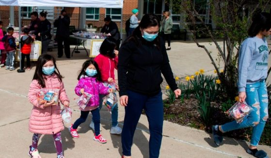Children, some wearing face masks, pick up free lunch at Kenmore Middle School in Arlington, Virginia on March 16, 2020, after schools in the area closed due to the coronavirus outbreak.
