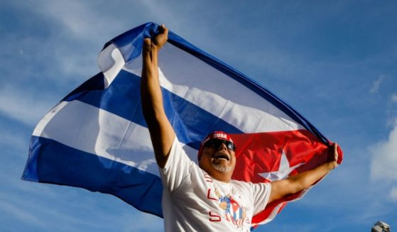 A man holds a Cuban flag Sunday during a demonstration showing support for Cubans protesting against their government, at Versailles Restaurant in Miami.