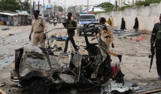 Police officers patrol by the wreckage of a car at the scene of suicide car bomb attack that targeted the city's police commissioner in Mogadishu, Somalia, on July 10. The al-Shabaab terrorist group claimed responsibility for the attack.