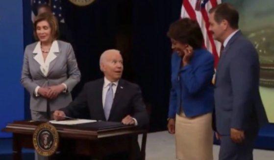 President Joe Biden signs a bill alongside California Democratic Congresswoman Maxine Waters on June 30, in Washington, D.C.